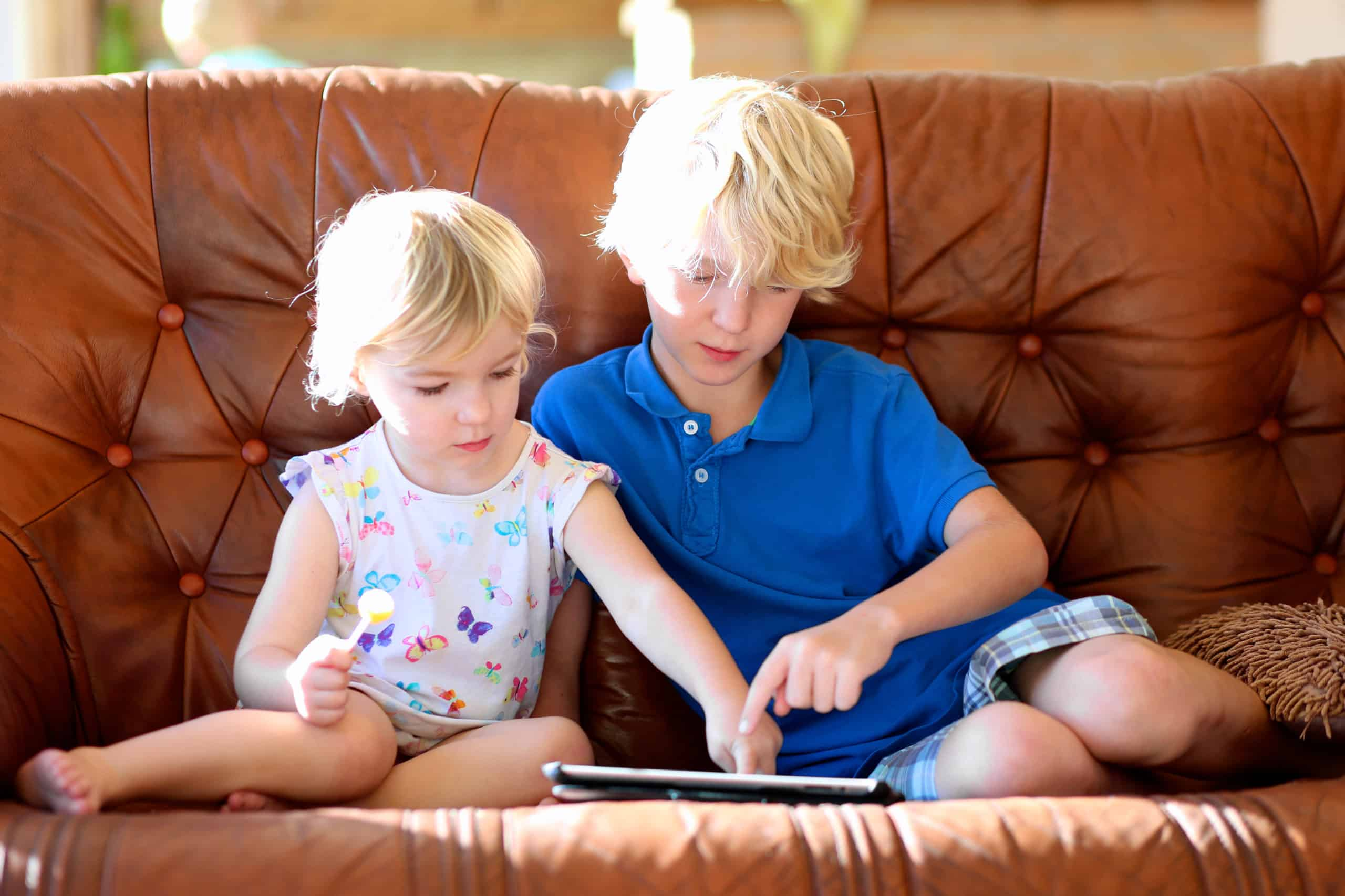Brother and sister playing with iPad Reading Aloud